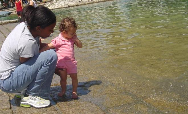 Rhema, age 1, timid about the water. I am with her, holding her hand as she prepares to take the first step.